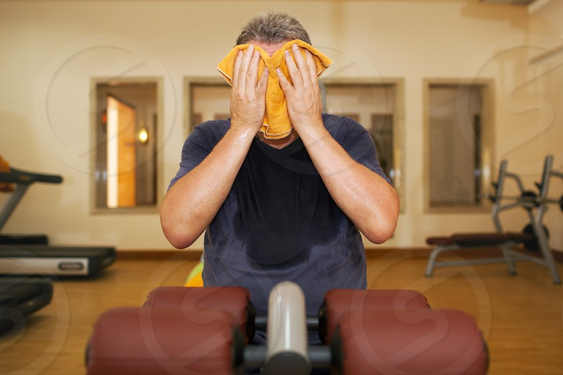 Man in the gymnasium after workout. He is sweaty exhausted and wiping the face with a towel photo