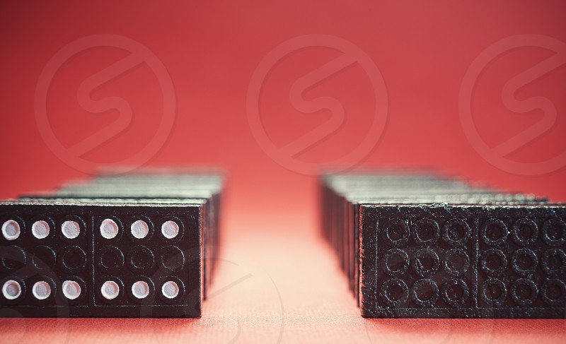 Two rows of dominoes background in blur and red.  photo