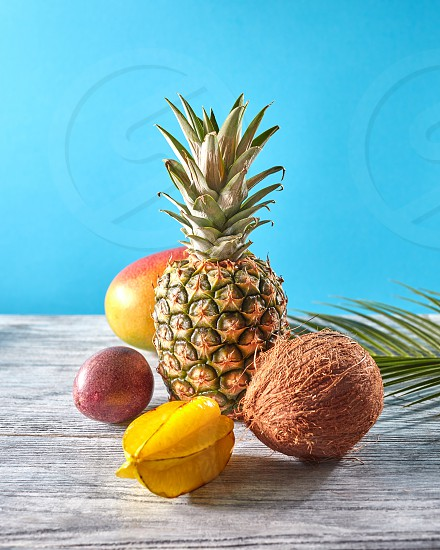 Summer composition with healthy exotic fruits - fresh pineapple carambola passion fruit coconut mango and palm leaf on a gray wooden table on a blue copy space. Concept of healthy dieting food. photo