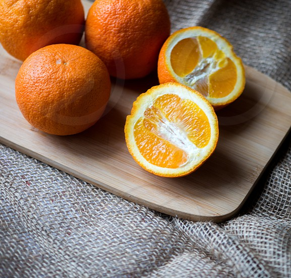 Orange fruits on wooden cutting board closeup of brown textured surfaceburlap texture background photo