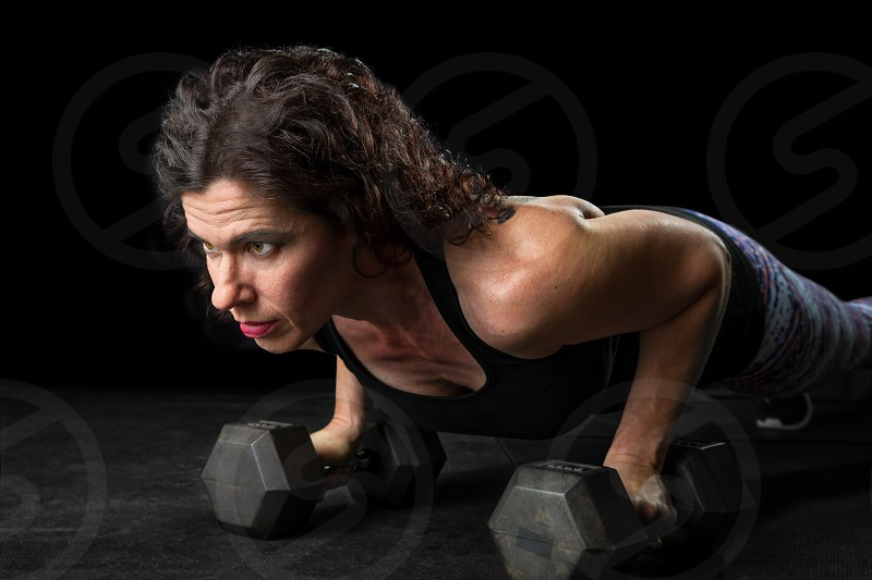 A female weightlifter holds a plank on dumbbells while staring intensely ahead.  She is against a black background and is cross lit. photo