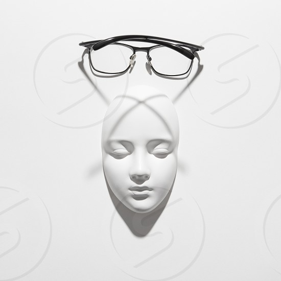 Glasses with plaster mask face for reading and person with visual impairment long shadows on a white background copy space. Top view. photo