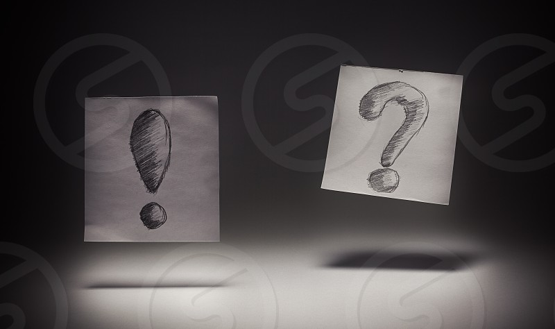Exclamation and question signs drawn on paper on gray background.  photo