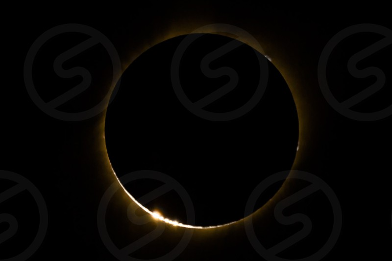 Totality of Great American Eclipse 2017 from Wind River area near Pinedale Wyoming showing diamond ring effect  or Baily's Beads and solar prominences large bright gaseous features extending outward from the Sun's surface often in a loop shape. Prominences are anchored to the Sun's surface in the photosphere and extend outwards into the Sun's corona. photo