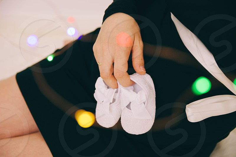 Pregnant Woman in Black Dress Holding Baby Shoes Closeup photo