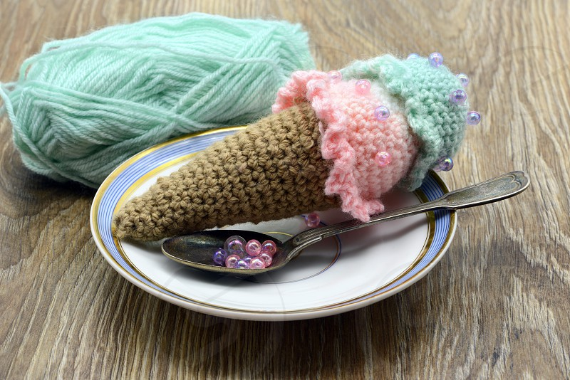 crochet ice cream cone with wool ball on table background photo