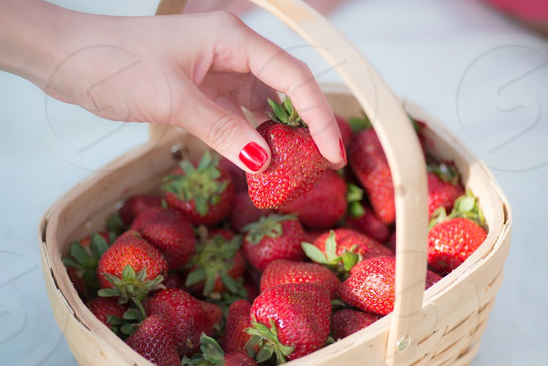 woman with red nail manicure picking red strawberry from brown woven basket photo