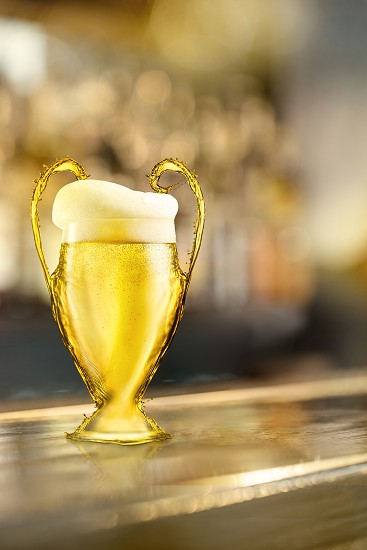 Football cup made of beer with foam on a wooden bar counter on a blurry background. As a symbol or emblem of the UEFA Champions League photo