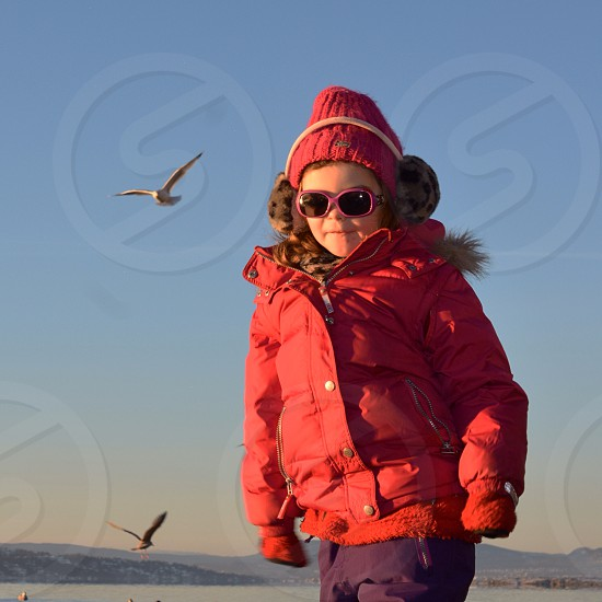 Learning to fly - girl - birds - seagulls - sky / water - sunglasses - happy - winter - sun photo