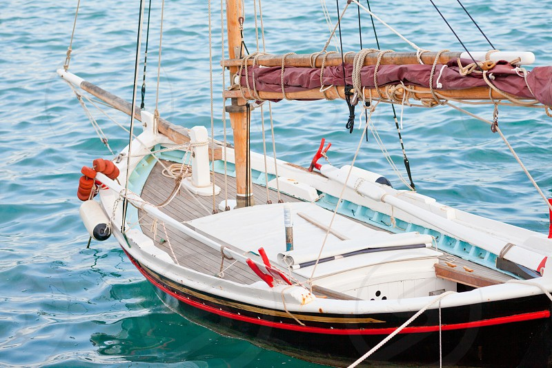 Ready to sail small traditional Greek sailboat in the water moored in harbor photo