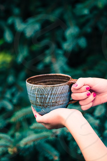 Female hand holding earthen cup with herbal tea with green natural background photo