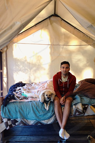 man in zip up hoodie and blue shorts sitting next to beige short coat small dog covered by pink white blanket on bed with blue bedspread and brown pillows inside beige tent photo
