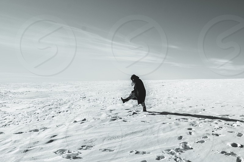 human wearing black coat while walking in a snow photo