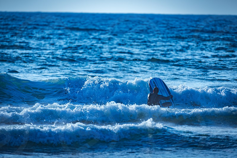Surfer about to catch a wave in monochromatic blue tones. photo