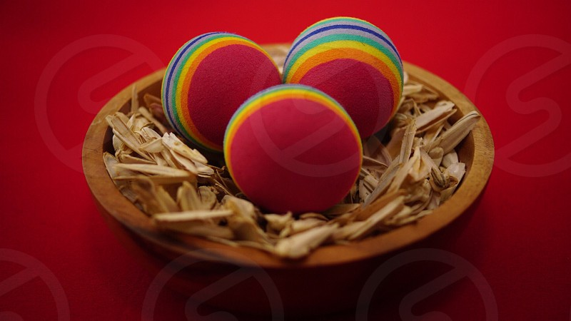 3 red yellow and blue round ball on a brown round bowl photo