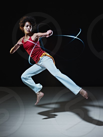 woman; sidekick; flying; kick; exercising; fighter; capoeira; 20s; active; adult; agility; american; art; attack; background; barefoot; black; brazilian; combat; copy space; exercise; female; fight; fitness; flexibility; foot; girl; gym; hispanic; indoor; latin; light; jumping; looking away; martial; mid-air; motion; movement; one person; people; power; self-defense; side; sport; sportswear; streak; strength; training; workout; young photo