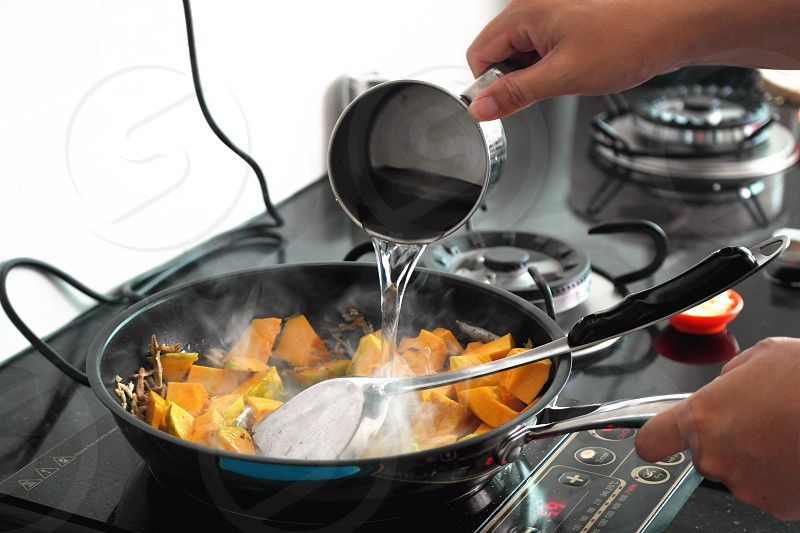 slice squash on frying pan with water photo