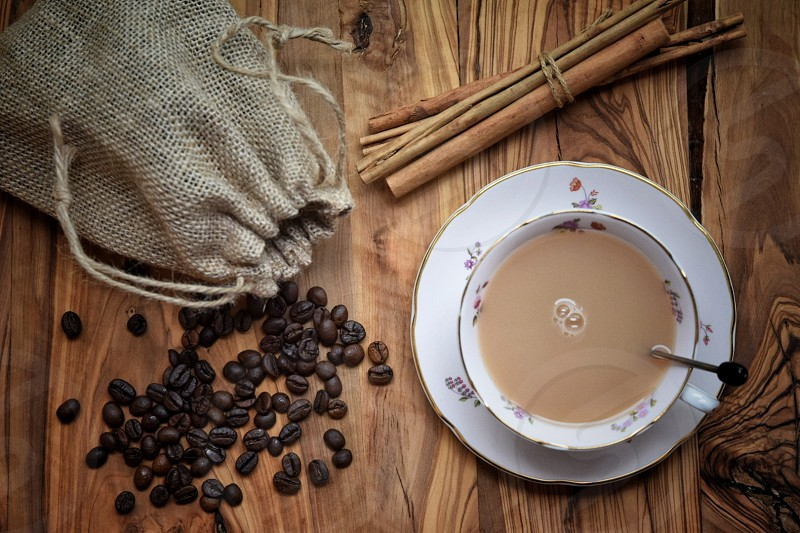 top view photography of white ceramic bowl with brown liquid content on plate and on top of wooden table with coffee beans beside drawstrings pouch photo