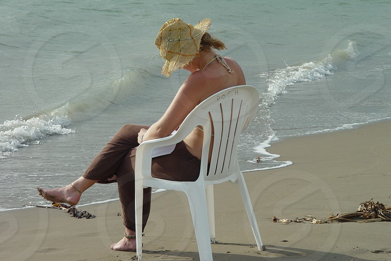 Young Woman Sitting on the beach. Beach Tourist Sitting Young Woman. photo