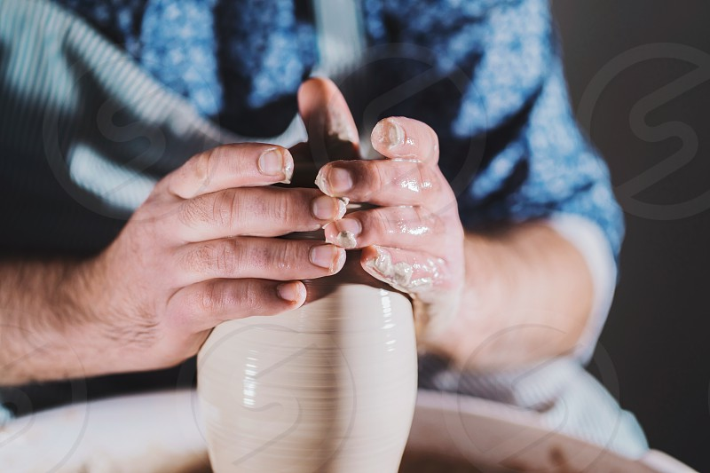 Artist operates hands which gently creating correctly shaped handmade from clay. Traditional pottery making teacher shows the basics of pottery in art studio photo