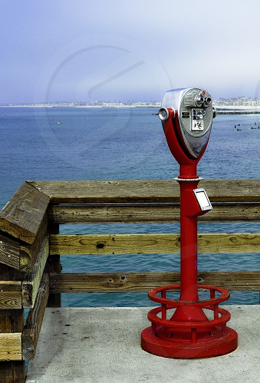 red and silver telescope on dock by shore photo