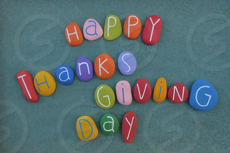 Happy Thanksgiving Day national holiday celebrated on various dates in Canada the United States some of the Caribbean islands and Liberia. Creative text composed with multi colored stone letters over green sand photo