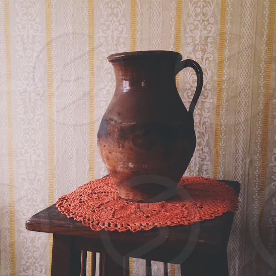 brown terracotta vase on table with orange place mat photo
