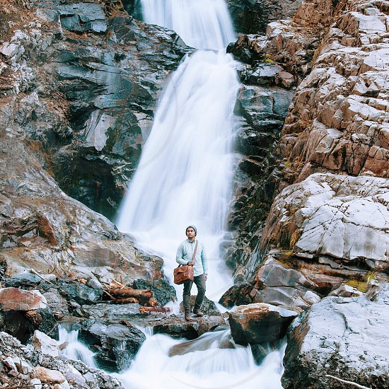 man in grey long sleeve shirt and grey pants with brown sling bag standing in front of a waterfall photo