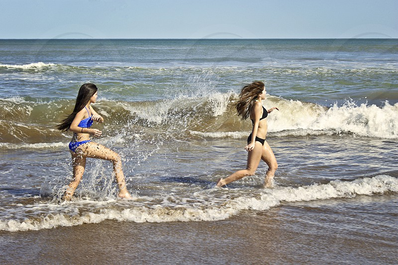 Two teenagers playing with the water splashing and laughing in a beach of Mar del PLata Argentina. photo