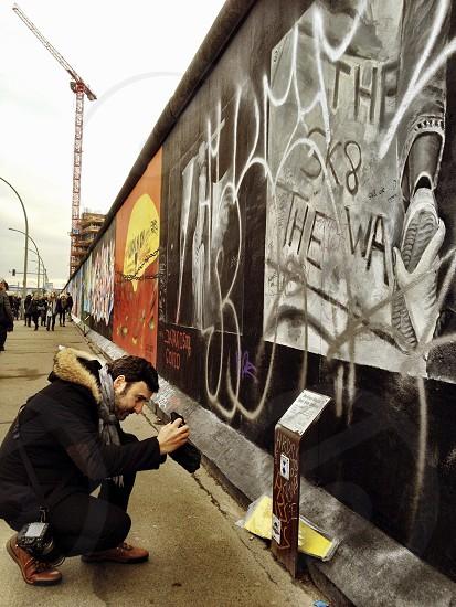 person using camera next to wall with graffiti photo