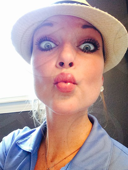 woman in blue polo shirt with white fedora kiss face photo