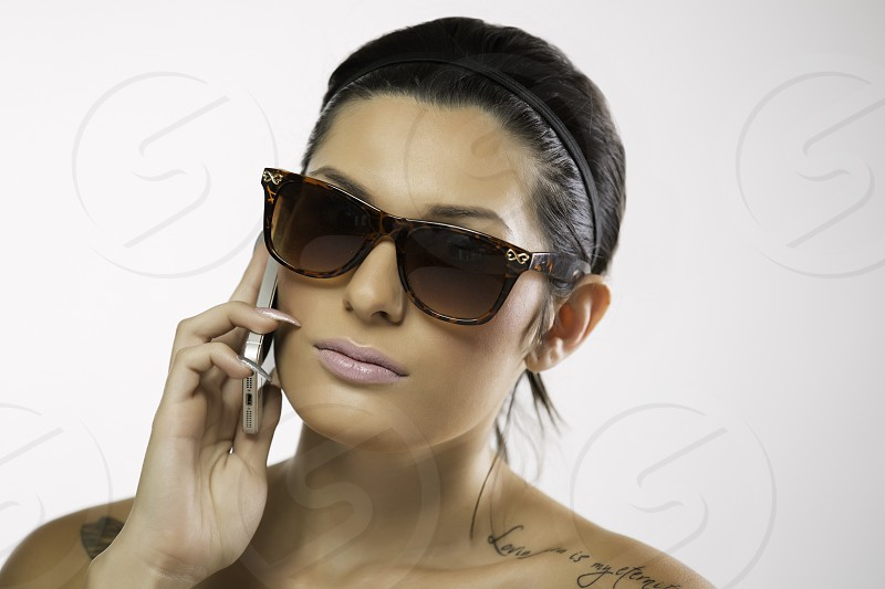 Sunglasses and phone with attitude photo