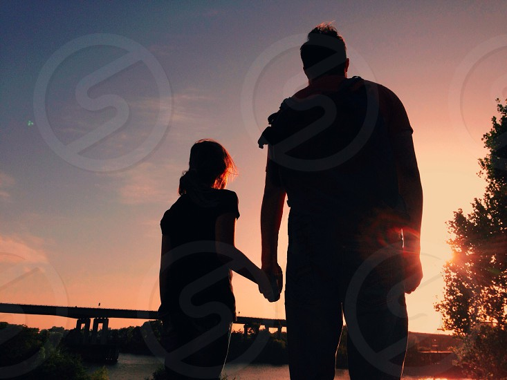 two people standing and watching the sunset photo