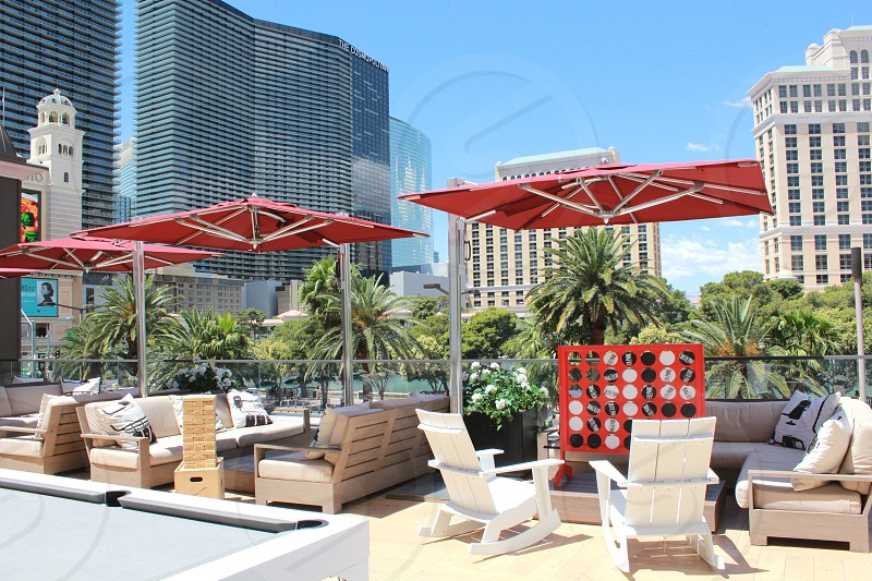 architectural photography of portable umbrella beside brown sectional sofa with green trees fronting 4 large high rise buildings photo