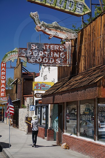 Sporting goods store in downtown Lone Pine California. Its neon sign advertises fishing gear with a large trout. photo