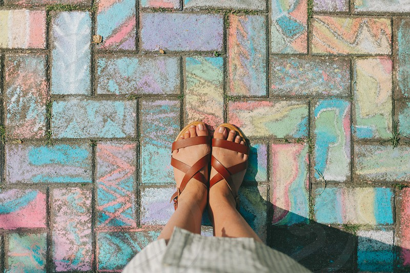 A woman looking down at her feet on the chalk covered ground.  photo