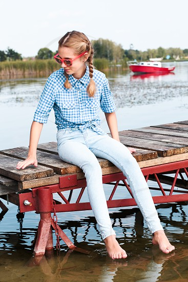 Young girl sitting on jetty over the lake and dipping feet in water on sunny day in the summertime photo