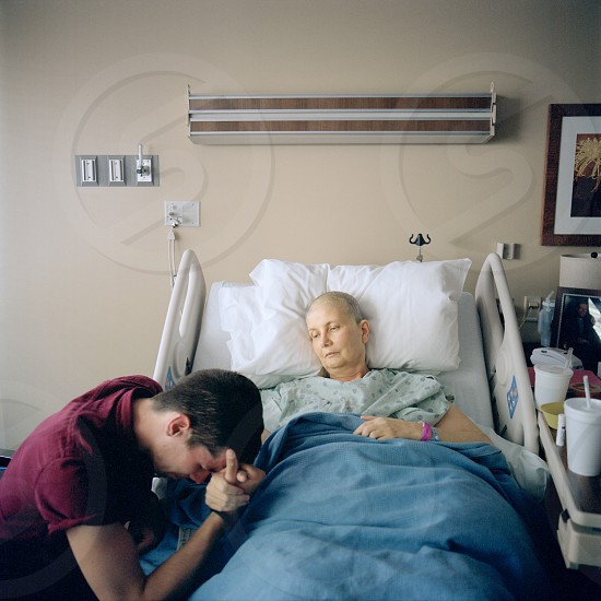 man holding woman hand lying on hospital bed photo