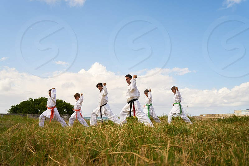 Hispanic men and children exercising in karate and traditional martial arts. Simulation of fight on the beach near the sea photo