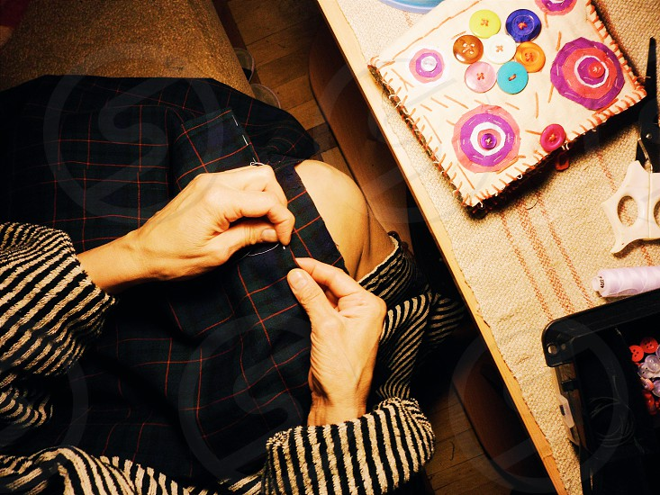 person fixing blue and green textile photo