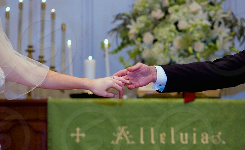couple reaching each others hand at the altar photo
