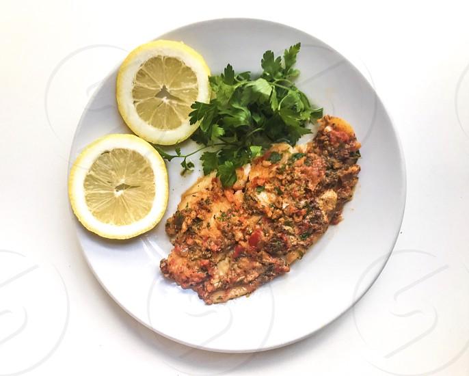 On the table  fish  fillet  flat lay  high key white  lemon  parsley  dish  white   overhead shot  photo