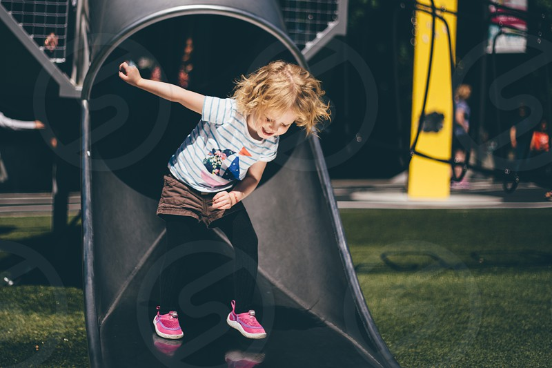 girl wearing white shirt and brown daisy dukes with black legging smiling while sliding on tube slide photo