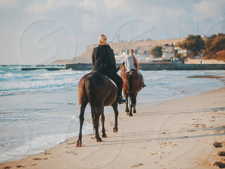 View of women riding beautiful horses wading through the sea splashing water drops around in golden light sunset or sunrise. Stallion walking in ocean water photo
