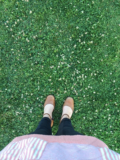 woman in black pants stepping on green grass photo