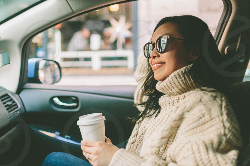 A woman in the car with a cup of coffee.  photo