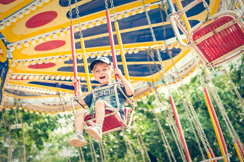boy happy fair carnival ride merry-go-round swings happy fun smile smiling blonde cap hat child youth play carousel ride amusement park giant great yellow blue red white trees green photo