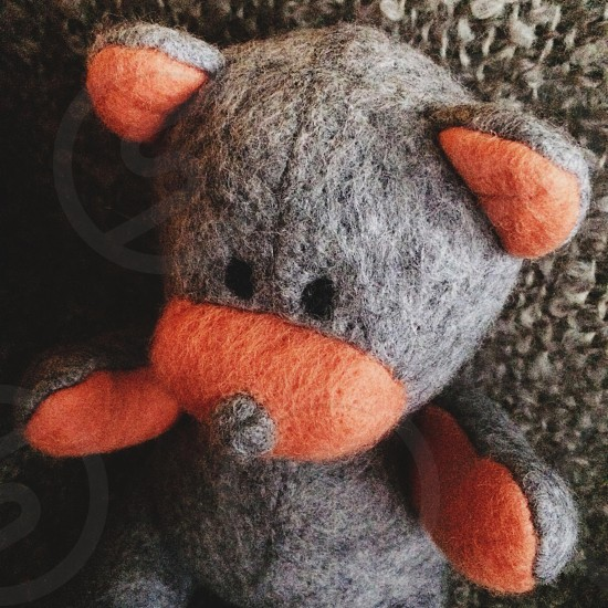 Grey and orange wool felt teddy bear against a brown woollen blanket photo