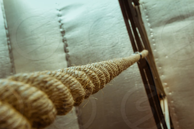 Brown climbing rope hanging from roof - Close up view from below photo