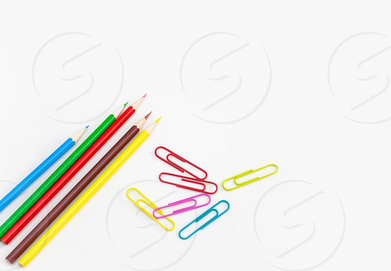 Stationery office supplies concept Colored crayon pencils with colorful clips on white background with copy space. Top view. photo